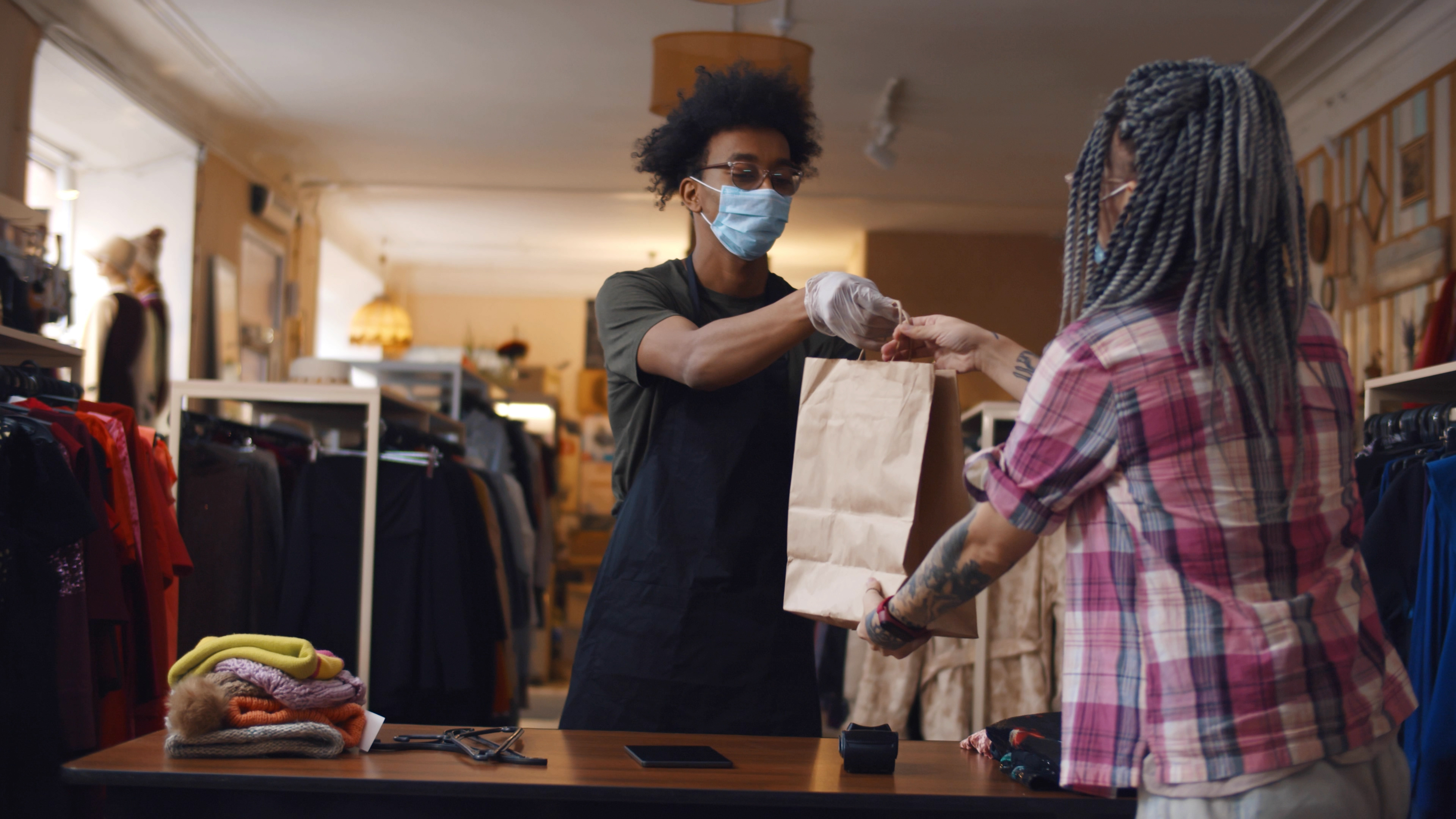 Young woman in safety mask purchasing in clothes store. African american shopkeeper man wearing medical mask and gloves working at clothing store