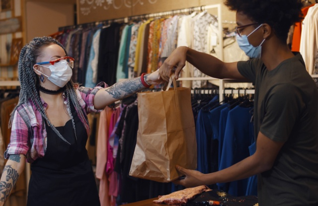 sales clerk at clothing store giving bag to woman