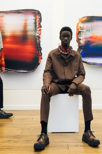 Looks from Berluti's fall 2021 collection with paintings by Lev Khesin.