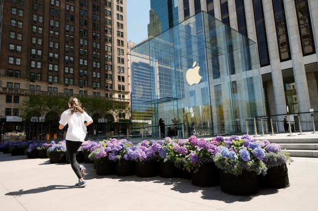 NEW YORK, NEW YORK - MAY 01: A jogger jogs past the Fifth Avenue Blooms Mother's Day installation in front of The Apple store on May 01, 2021 in New York City. (Photo by Michael Loccisano/Getty Images for Fifth Avenue Blooms Mother's Day Installation)