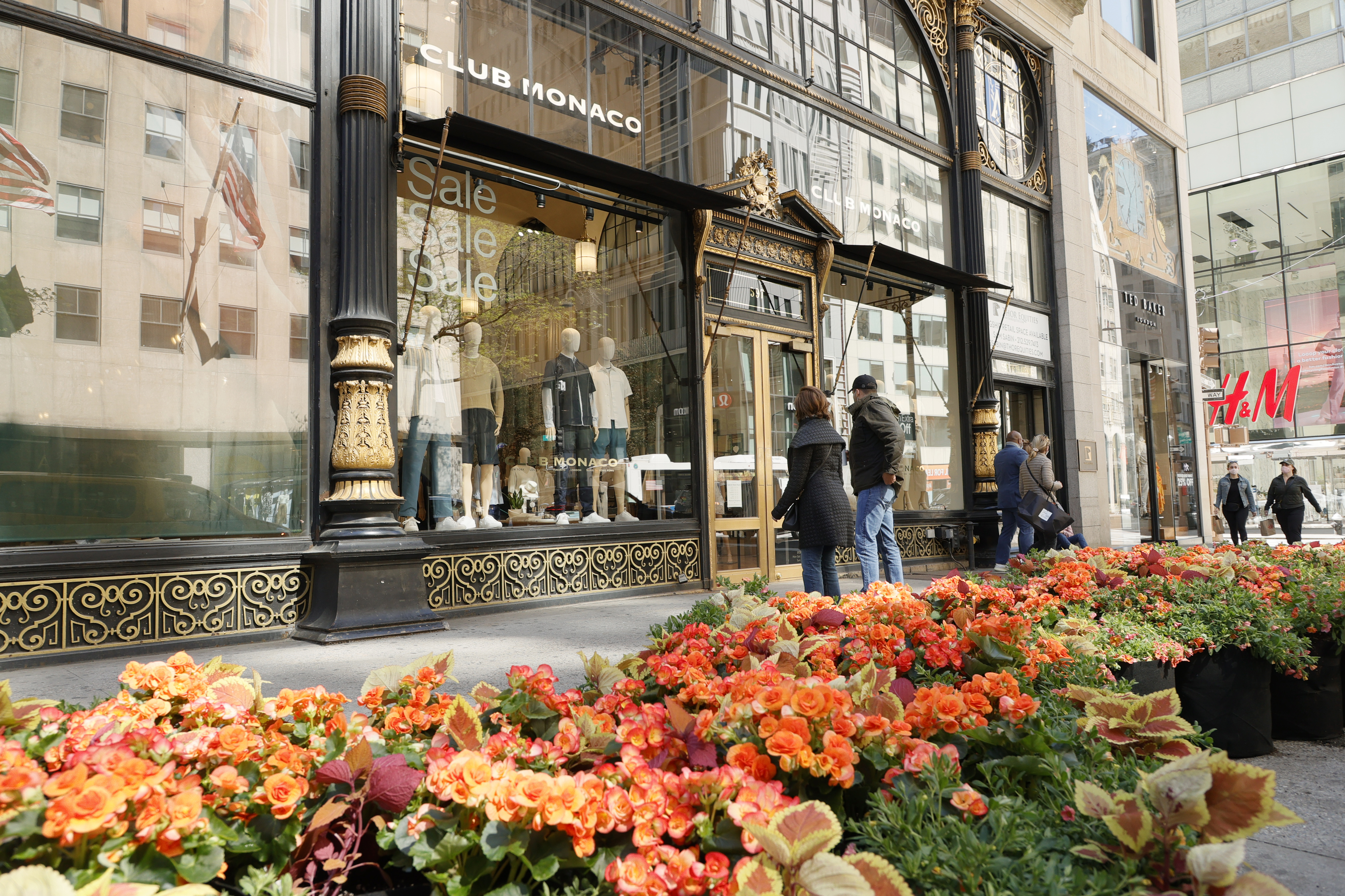 NEW YORK, NEW YORK - MAY 01: Pedestrians walk between Club Monaco and one of the Fifth Avenue Blooms Mother's Day floral installations on May 01, 2021 in New York City. (Photo by Michael Loccisano/Getty Images for Fifth Avenue Blooms Mother's Day Installation)