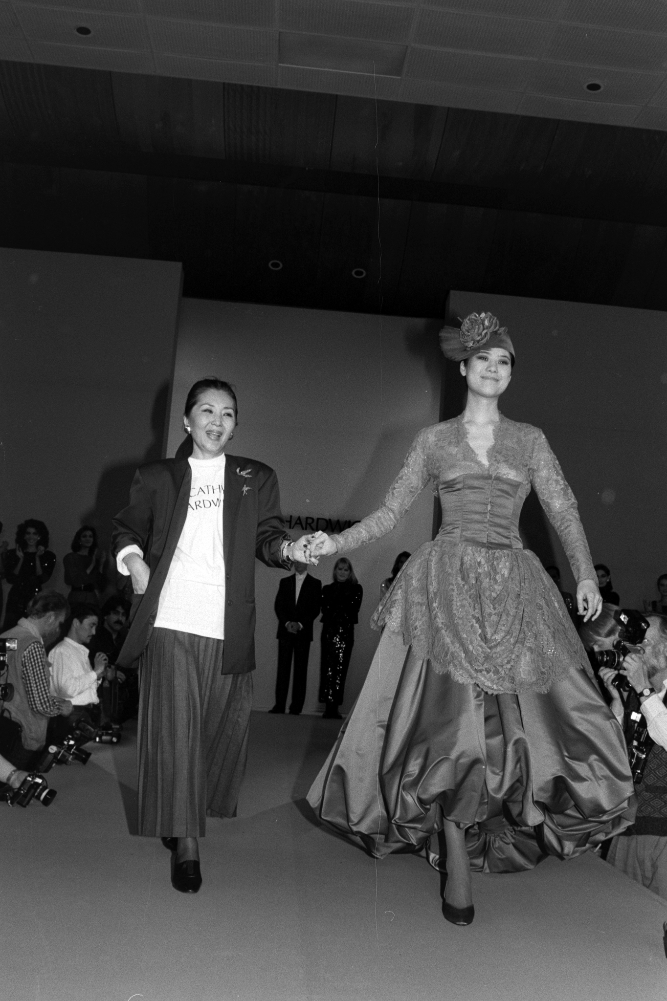 Designer Cathy Hardwick and model Ariane Koizumi walk her Fall 1986 Ready To Wear show finale.