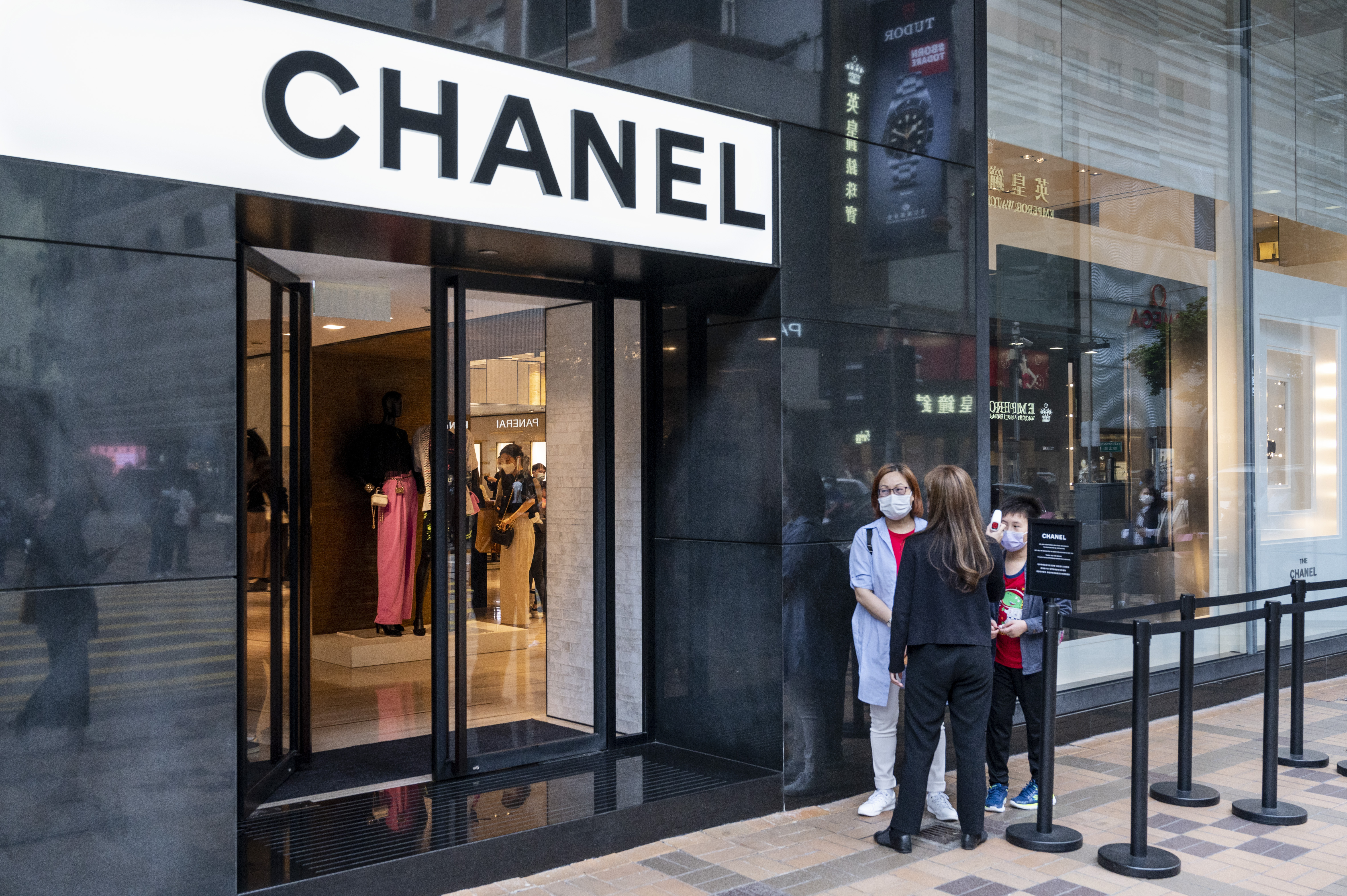 Shoppers in a queue at the entrance of the French multinational Chanel clothing and beauty products brand store seen in Hong Kong. (Photo by Budrul Chukrut / SOPA Images/Sipa USA)(Sipa via AP Images)