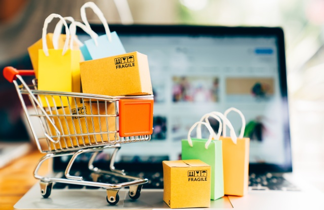 Product package boxes and shopping bag in cart with laptop computer which web store shop on screen for online shopping and delivery concept