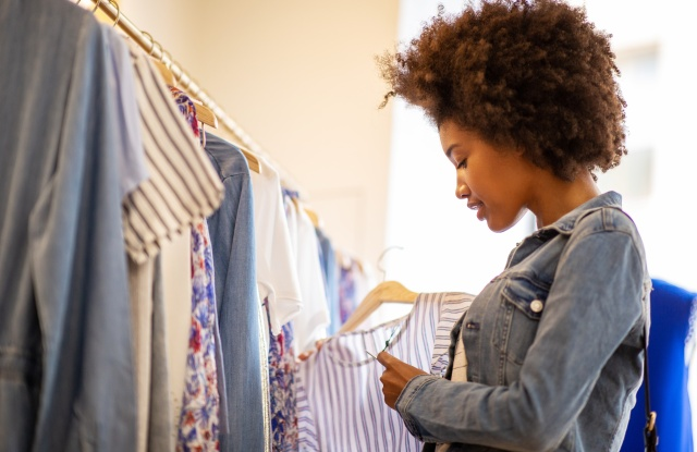 Side portrait of beautiful young black woman with afro  shopping for clothes in store