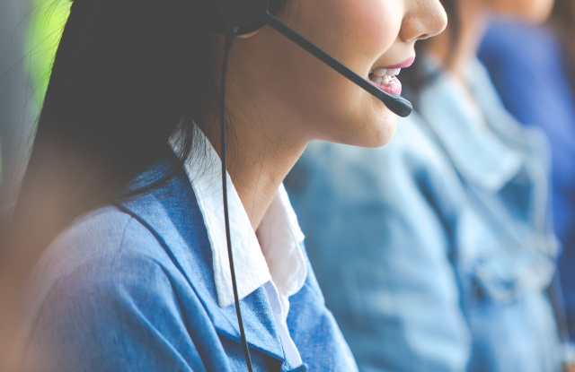 Attractive business woman Asian in suits and headsets are smiling while working with computer at office. Customer service assistant working in office
