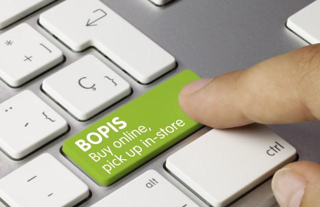 BOPIS buy online, pick up in-store Written on Green Key of Metallic Keyboard. Finger pressing key.
