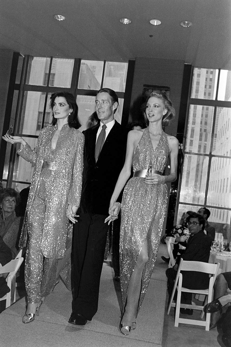 Designer Roy Halston with models Karen Bjornson and Margaret Donohue in looks from the Halston Made to Order Spring 1981 collection.