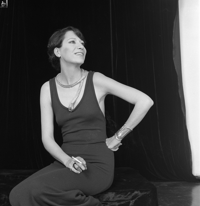 Jewelry designer Elsa Peretti models her snake charmer belt-necklace and bone cuff bracelet.