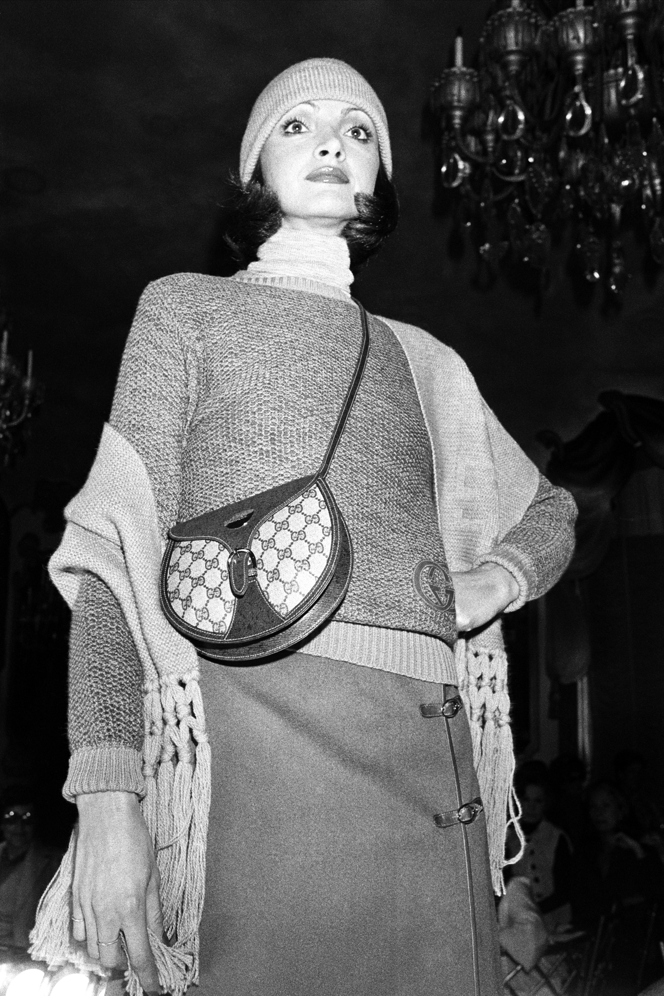 A model poses in Gucci's fall 1976 RTW collection and crossbody saddle bag  during a fashion show at the St. Regis Hotel.