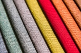 Colorful and bright fabric samples of furniture and clothing upholstery. Close-up of a palette of textile abstract diagonal stripes of different colors.