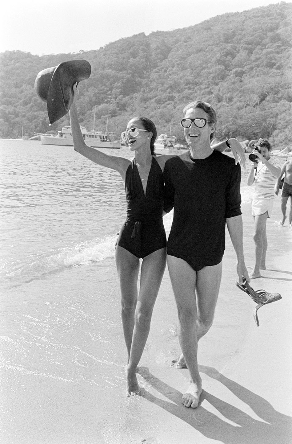 """Designer Roy Halston and model Pat Cleveland on the beach during Braniff's """"Three Evenings to Remember in Acapulco"""" event on March 16,1977."""