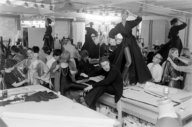"""Halston and assistants fit models Pat Cleveland on the tabletop, Chris Royer, Kyle Traylor, and Shirley Farro in """"body dressing"""" from Halston's Fall 1977 RTW advance."""