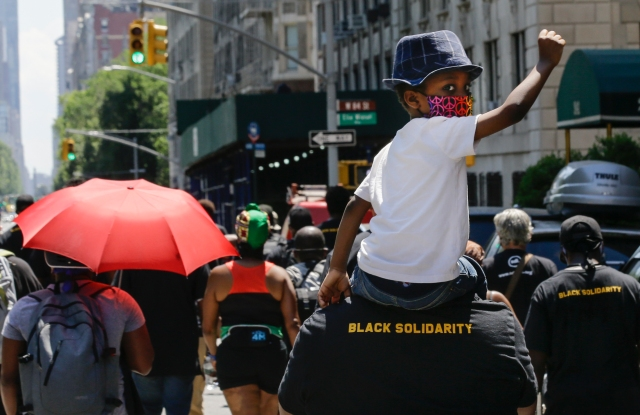 FILE - In this June 19, 2020, photograph, a man carries a child on his shoulders as they march near Central Park during a Juneteenth celebration, in New York. New York Gov. Andrew Cuomo signed legislation Wednesday, Oct. 14, 2020, officially making Juneteenth, a day commemorating the emancipation of enslaved people in the United States, a New York state holiday. Although President Abraham Lincoln issued the Emancipation Proclamation on Jan. 1, 1863, not everyone heard about it right away. It wasn't until June 19, 1865, that enslaved people in Galveston, Texas, found out about it from Union army personnel, making them among the last to know about their freedom. (AP Photo/Frank Franklin II, File)