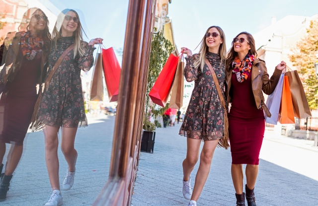 two women shoppers with bags looking in store window smiling