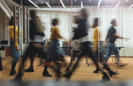 Businesspeople walking at modern office. Group of business employees at coworking center. Motion blur. Concept work process. Wide image