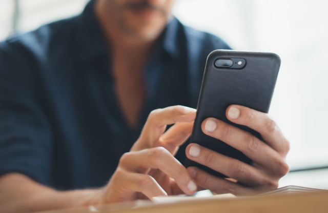 Close up photo of male hands with smartphone. Frreelancer at home office