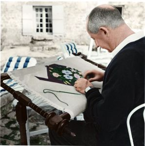 Christian Dior embroidering at his house in Milly-La-Forêt, in northern France