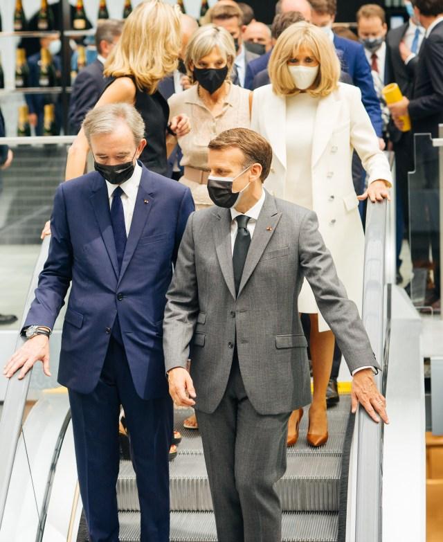 French President Emmanuel Macron and LVMH chief Bernard Arnault, accompanied by their spouses Brigitte Macron and Hélène Mercier-Arnault, take the escalator at the Samaritaine Paris Pont-Neuf department store.