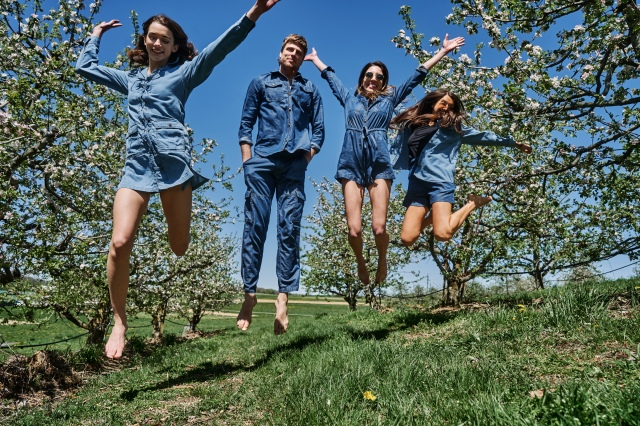 models wearing jeans and jumping in organic cotton field