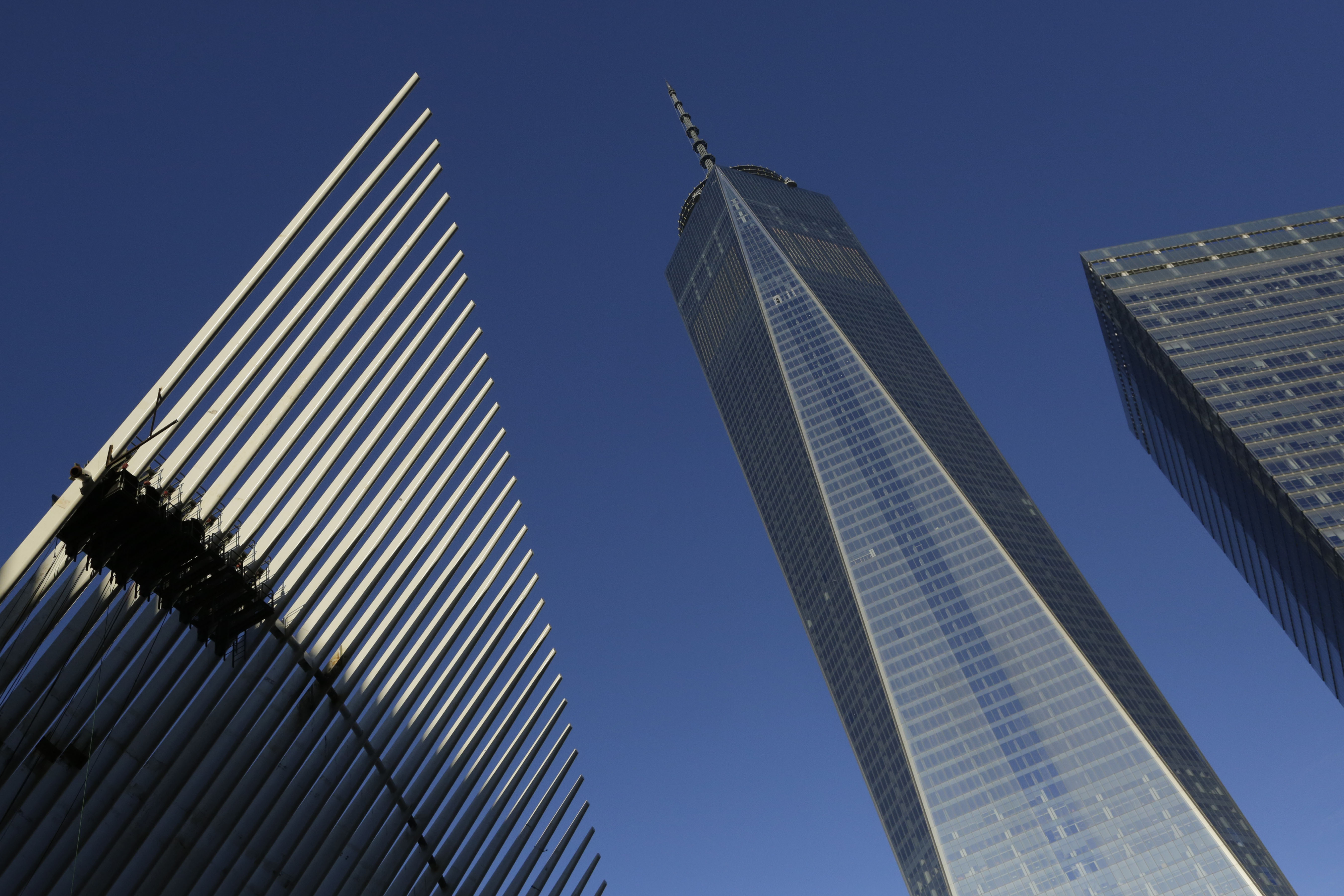One World Trade Center stands between the transportation hub, left, still under construction, and 7 World Trade Center, right, Monday, Nov. 3, 2014 in New York. Thirteen years after the 9/11 terrorist attack, the resurrected World Trade Center is again opening for business, marking an emotional milestone for both New Yorkers and the United States as a whole. Publishing giant Conde Nast will start moving Monday into One World Trade Center, a 104-story, $3.9 billion skyscraper that dominates the Manhattan skyline. (AP Photo/Mark Lennihan)