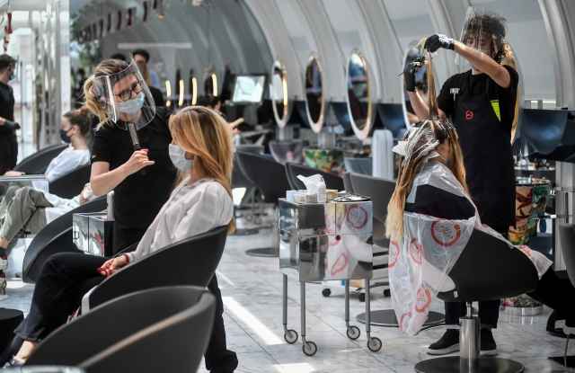 Clients get their hair done at a hairdresser in Milan, Italy, Monday, May 18, 2020 as Italy is slowly lifting sanitary restrictions after a two-month coronavirus lockdown. (Claudio Furlan/LaPresse via AP)
