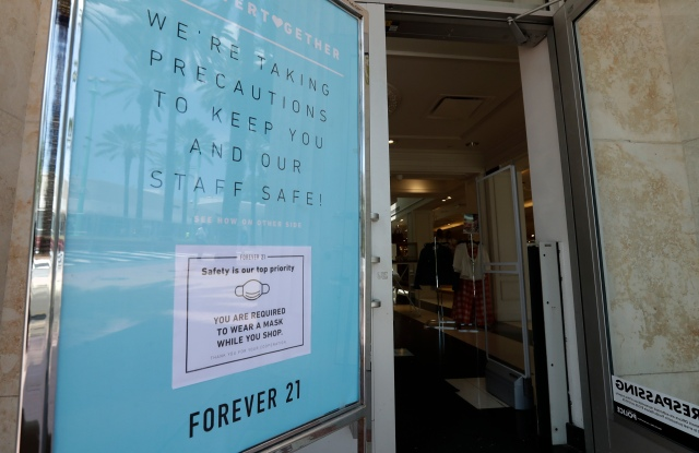 A sign outside a Forever 21 store on Miami Beach, Florida's famed Lincoln Road, advises shoppers that they must wear a mask to protect against the new coronavirus when entering the store, Wednesday, May 20, 2020. Miami, Miami Gardens, Hialeah and Miami Beach began phased openings of some shops Wednesday. (AP Photo/Wilfredo Lee)