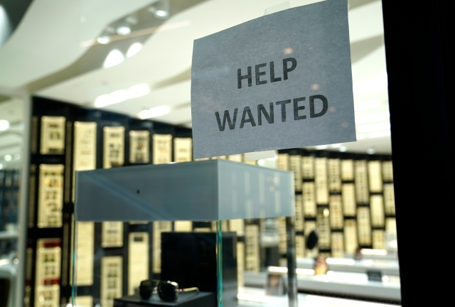 A Help Wanted sign is posted at a Designer Eyes store at Brickell City Centre, Friday, Nov. 6, 2020, in Miami. Defying fears of another slowdown, U.S. businesses kept hiring at a solid pace in October yet there are signs they remain cautious about the economy's future as the pandemic worsens. (AP Photo/Lynne Sladky)