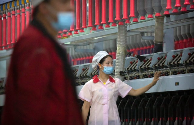 A worker checks machines processing cotton yarn at a Huafu Fashion plant, as seen during a government organized trip for foreign journalists, in Aksu in western China's Xinjiang Uyghur Autonomous Region, Tuesday, April 20, 2021. A backlash against reports of forced labor and other abuses of the largely Muslim Uyghur ethnic group in Xinjiang is taking a toll on China's cotton industry, but it's unclear if the pressure will compel the government or companies to change their ways. (AP Photo/Mark Schiefelbein)