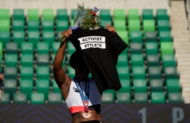 Gwendolyn Berry holds her T-shirt over her head during the metal ceremony after the finals of the women's hammer throw at the U.S. Olympic Track and Field Trials in Eugene, Ore. Tommie Smith, John Carlos and Berry are among the more than 150 educators, activists and athletes who signed a letter Thursday, July 22, urging the IOC not to punish participants who demonstrate at the Tokyo Games.