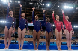 The United States' team wave prior to their women's artistic gymnastic qualifications performance at the 2020 Summer Olympics, Sunday, July 25, 2021, in Tokyo. (AP Photo/Natacha Pisarenko)