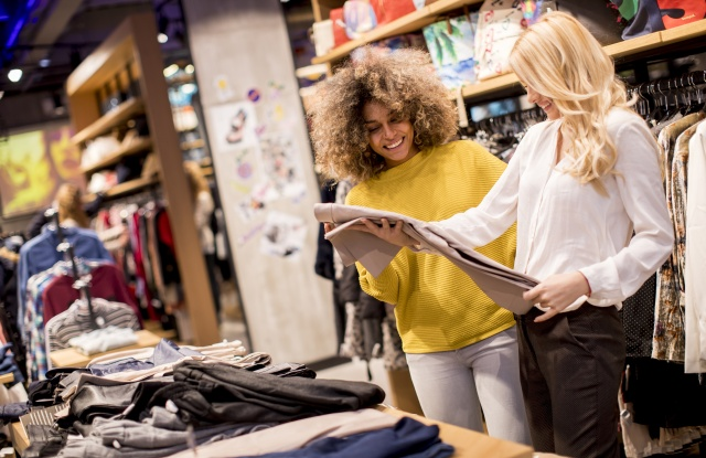 two young women shopping in clothing store