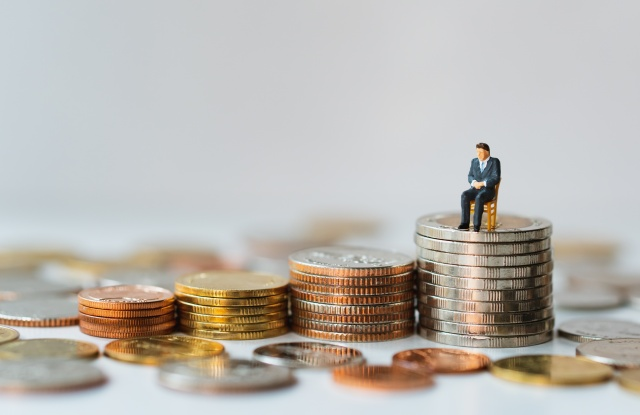 Miniature people, businessman sitting on stack coins using as business and financial concept