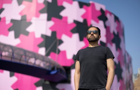 Osman Yousefzada in front of the Selfridges Birmingham covered with patterns designed by himself.