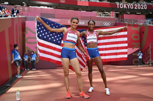 Sydney Mclaughlin, left, and Dalilah Muhammad, both of the United States, celebrate after finishing first and second respectively in the women's 400-meter hurdles during the 2020 Summer Olympics on Wednesday, Aug. 4, 2021, in Tokyo, Japan. (Andrej Isakovic/Pool Photo via AP)