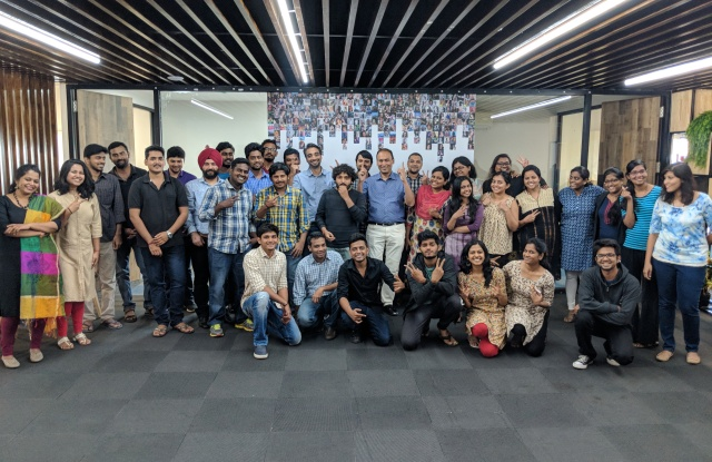 Poshmark CEO Manish Chandra (center, blue shirt), with staff at Poshmark India.