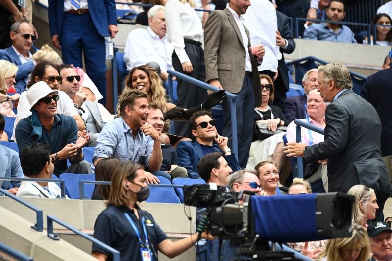 Alec Baldwin speaks with Brad Pitt, Bradley Cooper and Rami Malek during the Men's Singles championship match at the 2021 US Open, Sunday, Sep. 12, 2021 in Flushing, NY. (Garrett Ellwood/USTA via AP)